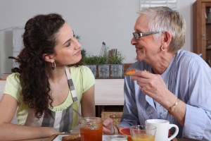 home care aide and elderly woman at breakfast