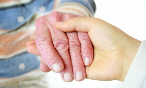 Senior citizen and yournger home care aide holding hands