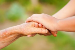 Home health aide holding hand of an elderly woman