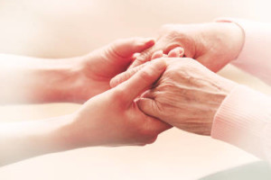 home care aide holding the hand of an elderly woman