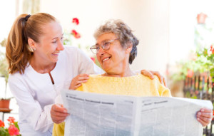 elderly woman and home care aid reading a newspaper