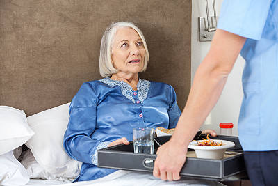 Home care aide serving dinner to elderly woman in bed