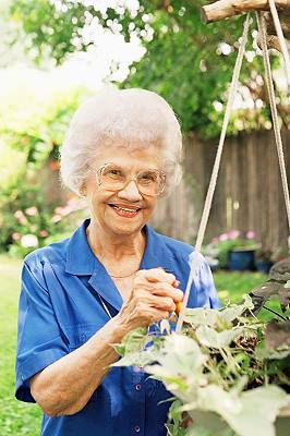 older woman with osteoporosis in her garden