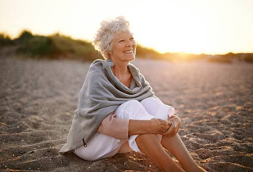 senior woman sitting on a beach making the most of aging: