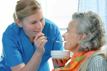 Home Care Aide Feeding Woman with Dementia