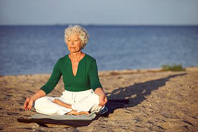 Older Baby Boomer Woman On Beach Meditating