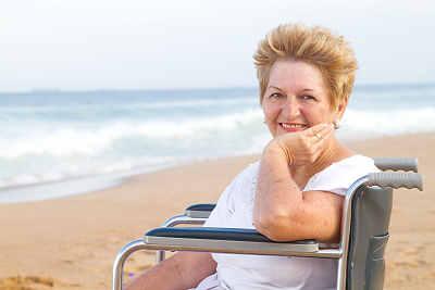 elderly Baby Boomer woman sitting on wheelchair on beach